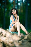 Beautiful Young Woman sitting on log posing Stock Photo