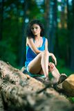 Beautiful Young Woman sitting on log posing Stock Image