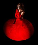 Beautiful young woman sitting in a long red evening dress Stock Image