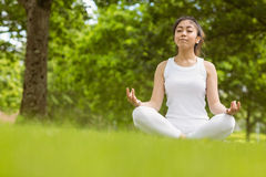 Beautiful young woman sitting in lotus pose at park Royalty Free Stock Images