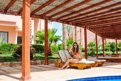 Beautiful young woman sitting on a lounger by the pool Royalty Free Stock Images