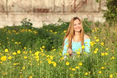 Beautiful young woman sitting in meadow Royalty Free Stock Image