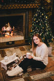 Beautiful young woman sitting near fireplace under the Christmas tree drinking cocoa with marshmallow Royalty Free Stock Photo