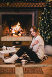 Beautiful young woman sitting near fireplace under the Christmas tree drinking cocoa with marshmallow Stock Photography