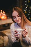 Beautiful young woman sitting near fireplace under the Christmas tree drinking cocoa with marshmallow Stock Photo