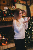 Beautiful young woman sitting near fireplace under the Christmas tree drinking cocoa with marshmallow Stock Image