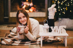 Beautiful young woman sitting near fireplace under the Christmas tree drinking cocoa with marshmallow Royalty Free Stock Image