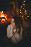 Beautiful young woman sitting near fireplace under the Christmas tree drinking cocoa with marshmallow Royalty Free Stock Photography