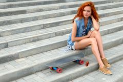 Beautiful young woman sitting near a skateboard Royalty Free Stock Images