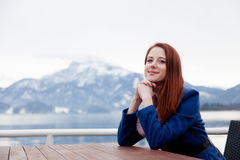 Beautiful young woman sitting near table on the mountains backgr Royalty Free Stock Photos