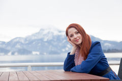 Beautiful young woman sitting near table on the mountains backgr Stock Image