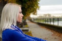 Beautiful young woman sitting outdoor on cloudy autumn day Royalty Free Stock Images