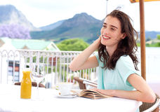 Beautiful young woman sitting outside at cafe with book Stock Image