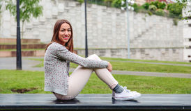 Beautiful young woman sitting on park bench Royalty Free Stock Images
