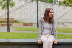 Beautiful young woman sitting on park bench Stock Photo
