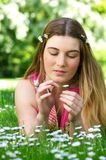 Beautiful young woman sitting in the park picking flower petals Royalty Free Stock Photos
