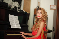 Beautiful young woman sitting at the piano in the room Royalty Free Stock Image