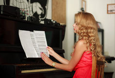 Beautiful young woman sitting at the piano in the room Stock Photography