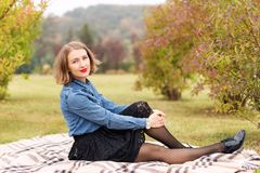 Beautiful young woman sitting on a plaid in autumn park. Season and people concept. Fashion model having fun in fall Royalty Free Stock Images