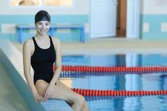 Beautiful young woman sitting at pool and looking at camera. Stock Image