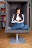 Beautiful young woman sitting and reading Stock Images