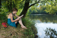 Beautiful young woman sitting by the river and read a book Royalty Free Stock Photos