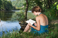 Beautiful young woman sitting by the river and read a book Royalty Free Stock Photo