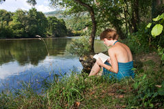 Beautiful young woman sitting by the river and read a book Stock Images