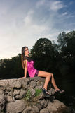 Beautiful young woman sitting by the river Stock Photography