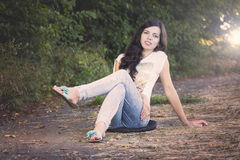 Beautiful young woman sitting on road in park Stock Images