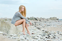 Beautiful young woman sitting on rock. Over sea at summer Stock Photography