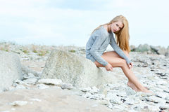 Beautiful young woman sitting on rock. Over sea at summer Royalty Free Stock Photos