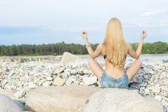 Beautiful young woman sitting on rock. Over sea at summer Stock Photo
