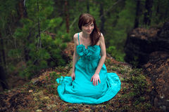 Beautiful young woman sitting on a rock in the woods. Beautiful young woman wearing elegant white dress sitting on a rock in the woods royalty free stock photos