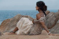 Beautiful young woman sitting on sand at the beach stock photography