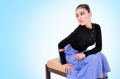 Beautiful young woman sitting with sexy pose. On blue background Stock Photo