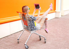Beautiful young woman sitting in shopping trolley cart over colorful orange Stock Photography
