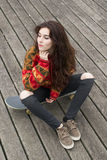 Beautiful young woman sitting on skateboard looking away. Royalty Free Stock Images