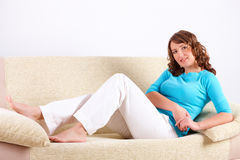 Beautiful young woman sitting on sofa Stock Photography