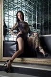 Beautiful young woman sitting on sofa in nightclub Stock Photo