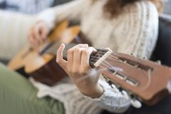 Beautiful young woman sitting on sofa playing guitar. Focus on hand Royalty Free Stock Photography