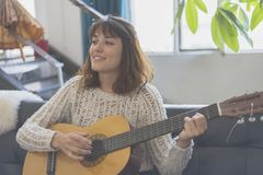 Beautiful young woman sitting on sofa playing guitar. And smliing Royalty Free Stock Photography