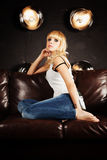 Beautiful young woman sitting on sofa Royalty Free Stock Photos