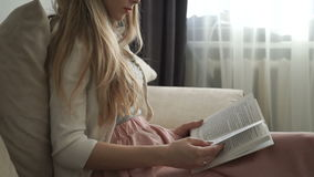 Beautiful young woman sitting on sofa reading book and smiling stock video