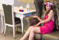 Beautiful young woman sitting on the sofa royalty free stock image