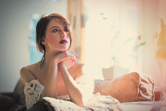 beautiful young woman sitting on the sofa in the room Royalty Free Stock Photography