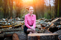 Beautiful young woman sitting on stack of felled tree trunks in the forest Royalty Free Stock Photos