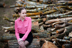 Beautiful young woman sitting on stack of felled tree trunks in the forest Royalty Free Stock Image