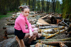 Beautiful young woman sitting on stack of felled tree trunks in the forest.  Stock Photo