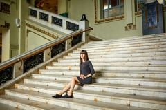 Beautiful young woman sitting on the steps stock photos